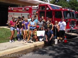 Fire fighter Dan Fabry posing for a picture with the community service group from Ursinus College.
