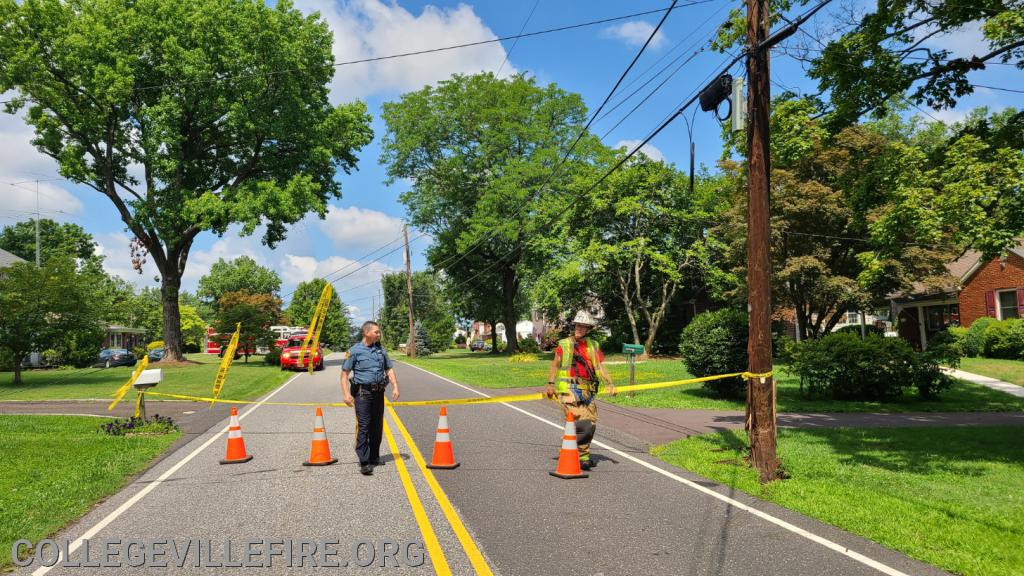 Detective Milburn and Chief 77 placing caution tape across the roadway and on the phone/cable lines